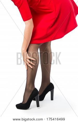 Woman in the red dress stockings shoes with high heels and with her hand on the leg - isolated on white