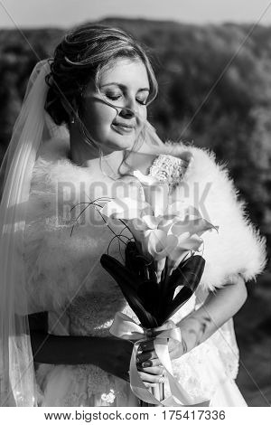 Happy Gorgeous Bride Posing And Holding Bouquet Of Callas On Background Of Sunny Trees Forest, Sweet