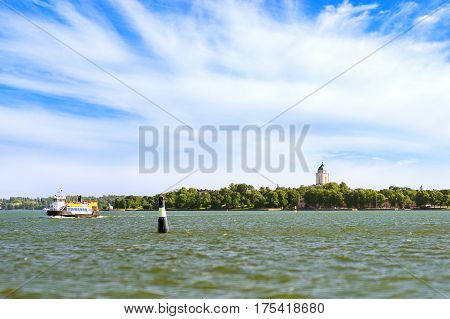 Tourist passenger boat sails near sea buoy on background of island Suomenlinna. Sea walk by motorboat in Nordic fjords. Suomi Helsingfors South Gulf