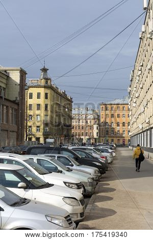 cityscape view of the city of Saint-Petersburg Sablinskaya street cars parked along the road on the sidewalk there are people buildings blue sky architecture Russia