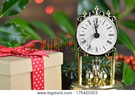 Vintage clock showing midnight and gift box with red ribbon