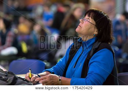 Mature female Referee on Rock climbing Competitions watching Athlete, colorful Audience on blurred Background. National Climbing Championship, Dnipro, Ukraine, May 21, 2016
