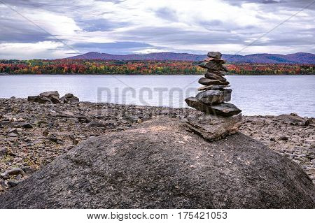 Autumn Inukshuk on a rock near a calm lake on a cloudy sky with beautiful colored trees in background