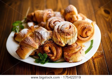 Sweet buns with jam on a wooden table