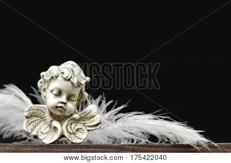 Angel figurine with feather wings on dark background