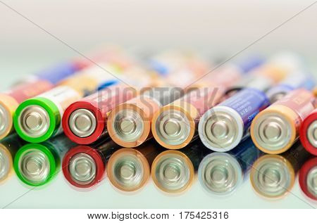 Closeup of pile of used alkaline batteries. Close up colorful rows of selection of AA batteries energy abstract background of colorful batteries. Alkaline battery aa size. Storage batteries in rows.
