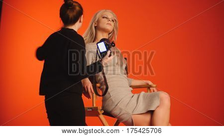 Blonde model girl in photo studio - photographer straightens hair, fashion backstage, red background