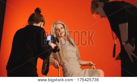 Blonde model girl lying in photo studio - photographer and make up artist straightens hair, fashion backstage, red background
