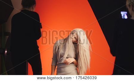 Fashion backstage: blonde girl model plays long hair - photographer take a picture in studio, red background