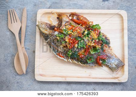 Thai fried Tilapia cuisine Spicy and sour herb on wooden tray