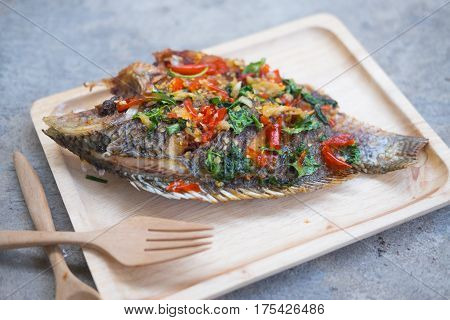 Thai style fish menu deep fried in chili sweet sauce on wooden tray