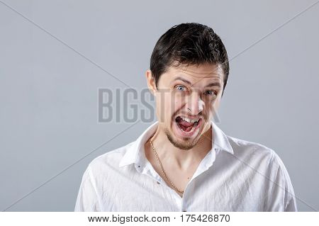 angry young man brunette in the white shirt screaming on a grey background.