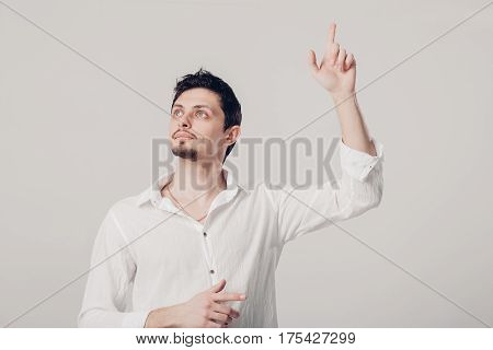 young man with an idea raising his finger in the air on gray background. gesture Eureka. soft light