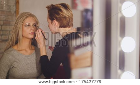 Visage - makeup artist and blonde model near mirror in the dressing room, close up
