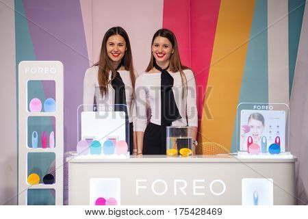 ZAGREB, CROATIA - MARCH 2, 2017: Two hostesses present Foreo LUNA mini facial cleansing brushes and IRIS eye massager at Foreo's display