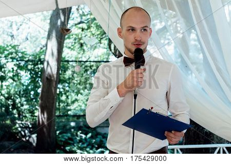 stylish handsome emcee performing speech for toast at wedding reception