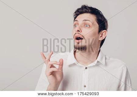 portrait of young attractive surprised brunette male in white shirt on gray background. soft, light