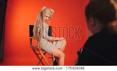 Blondy female posing for photographer - fashion backstage red background