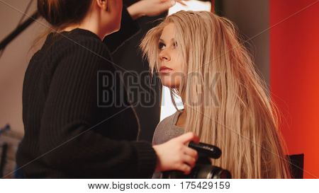 Blonde white caucasian model girl in photo studio - photographer straightens hair, fashion backstage, red background