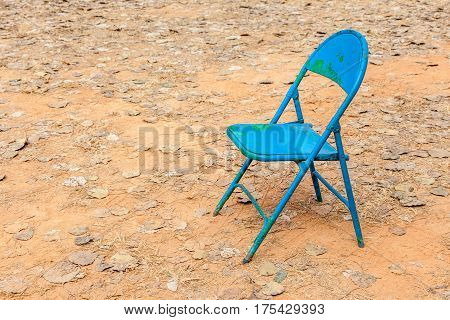Old rusty foldable blue chair leave alone in abandoned dried backyard and fallen leaves on ground.