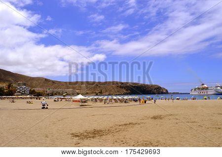 Los Cristianos beach Tenerife Canary Islands Spain Europe - June 15 2016: Tourists on the beach enjoying the sun