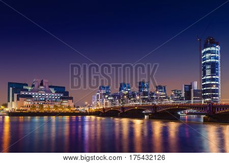 MI6 Building, St George Wharf, The Tower and Vauxhall Bridge on the Thames at night, London, UK