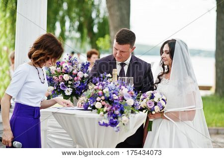Wedding couple sign a document on registration table with master of ceremony.