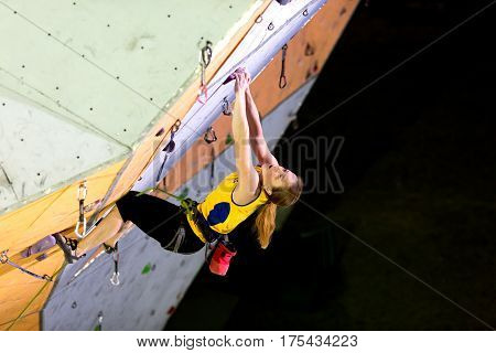 Female Climber hanging on Climbing Wall. National Climbing Championship, Lead climbing Finals, Dnipro, Ukraine, May 21, 2016