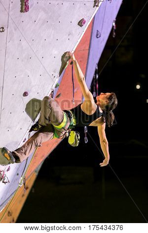 Cute female Athlete hanging on climbing Wall trying to relax before next move in night spotlight illumination