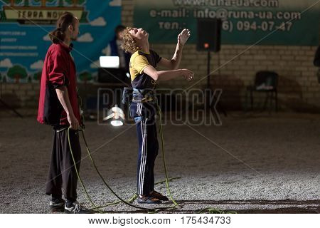 Young Rock Climber preparing for Try planning and imitating his future moves. Belaying referee staying aside. Night illumination. National Climbing Championship, Dnipro, Ukraine, May 21, 2016