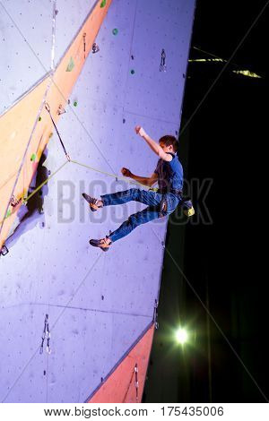 Male climber flying after failed try spilling of climbing wall in a night illumination light. Ukrainian National Climbing Championship, Lead climbing Finals. Dnipro, Ukraine, May 21, 2016