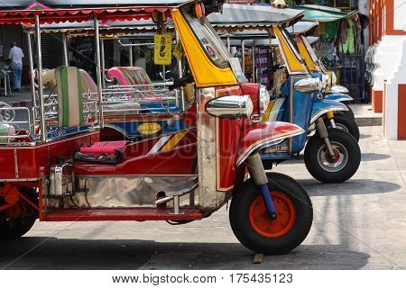 Colorful Tuk Tuk taxis parked outside a temple in Bangkok Thailand.