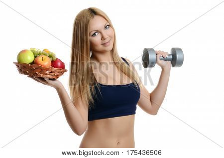 Beautiful blonde girl holding an apple and a dumbbell on white
