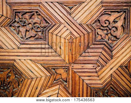 Detail of an intricately carved wooden door at Alhambra Fort in Granada Spain.