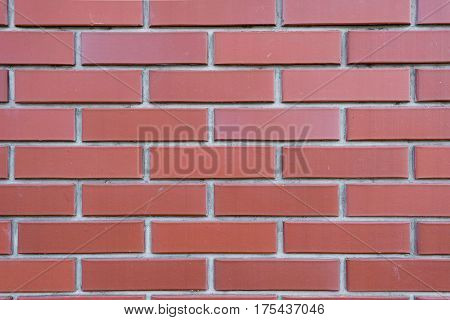 Brick wall of red brick with elements of concrete