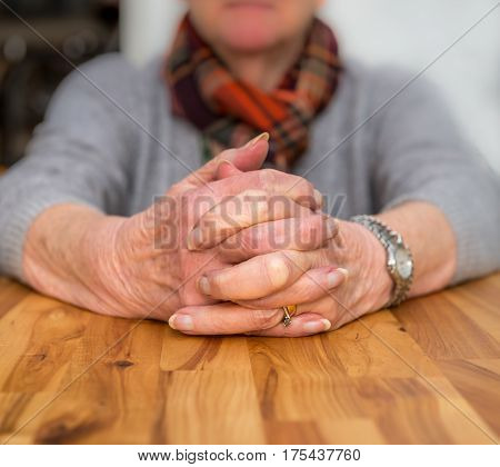 Clasped Hands Of An Elderly Lady Sitting At A Table.