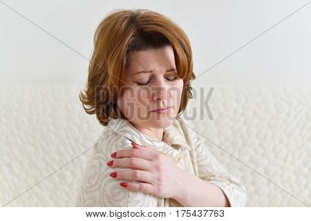 Beautiful woman holding her hand on a sore shoulder