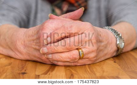 Clasped Hands Of A Female Pensioner Resting On A Table.