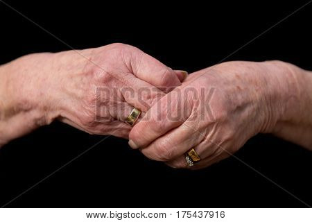 Widows Hands Clasped In Grief On A Black Background.