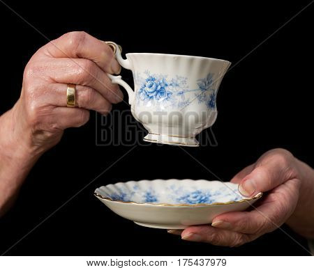 Teacup And Saucer Held In An Old Woman's Hands.