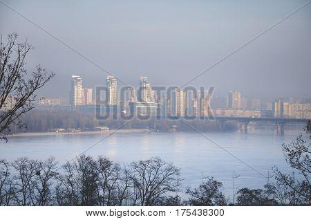 Modern buildings in the haze in smog on the banks of the Dnieper River in the spring Kiev Ukraine
