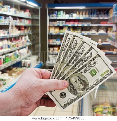 man's hand holding money on shopping in the supermarket