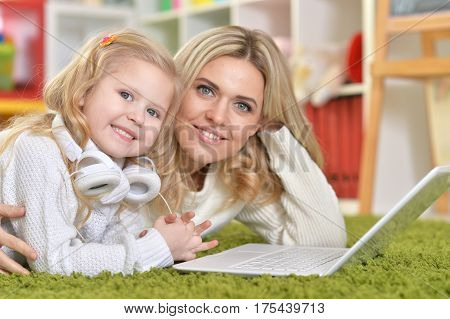 Portrait of a mother with little daughter using laptop