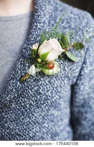 Gentle groom boutonniere with roses and beads. Close up