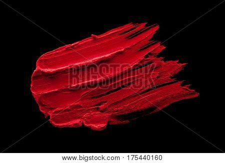 Red lipstick smudged on a black isolated background