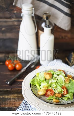 Healthy Grilled Chicken Caesar Salad with Cheese and Croutons on the wooden table