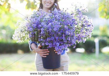 Happy woman florist with bouquet of flowers bucket outdoors. Close up