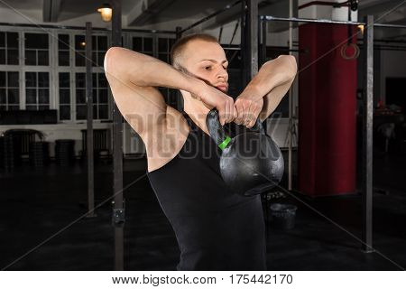 Portrait Of An Athlete Man Exercising With Kettle Bell In The Gym