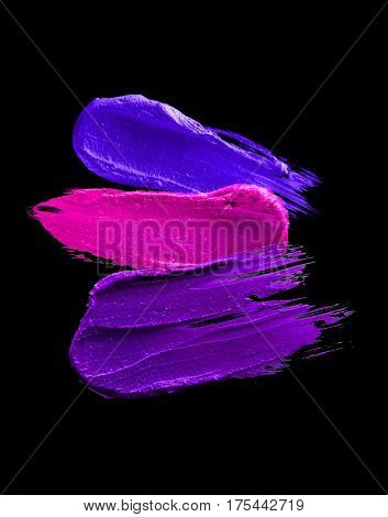 Multicolored lipstick smudged on a white isolated background