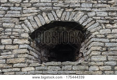 Background of old gray stone wall with embrasure in Krom (Kremlin) of Pskov